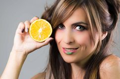 Headshot brunette with dark mystique look and green lipstick, holding up an orange next to face looking into camera Stock Photography