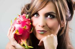 Headshot brunette, dark mystique look and green lipstick, holding up pink pitaya fruit, looking into camera Stock Photography