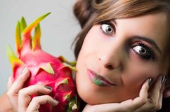 Headshot brunette, dark mystique look and green lipstick, holding up pink pitaya fruit, looking into camera Royalty Free Stock Photo