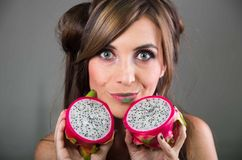 Headshot brunette, dark mystique look and green lipstick, holding up two open halfs of pink pitaya fruit with both hands Royalty Free Stock Image