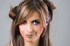 Headshot brunette with dark mystique look and green lipstick posing for camera, grey background Royalty Free Stock Photography
