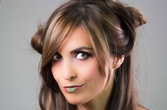 Headshot brunette with dark mystique look and green lipstick posing for camera, grey background Royalty Free Stock Image