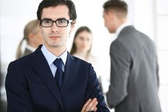 Headshot of businessman standing straight with colleagues at background in office. Group of business people discussing. Questions at conference or presentation royalty free stock image