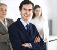 Headshot of businessman standing straight with colleagues at background in office. Group of business people discussing. Questions at conference or presentation royalty free stock photography