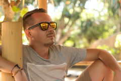 Headshot of a caucasian man in his late twenties with designer stubble wearing aviator sunglasses. Outdoors, tropical Stock Photo