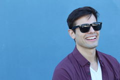 Headshot of a Caucasian man in his mid twenties with designer sunglasses taken against a plain blue background with copy space Royalty Free Stock Images