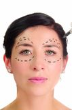 Headshot caucasian woman with dotted lines drawn around eyes looking into camera, preparing cosmetic surgery Royalty Free Stock Photo