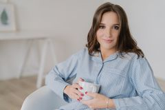 Headshot of Caucasian woman with make up, dressed in pyjamas, holds mug of tea, sits in comfortable armchair, enjoys good rest at royalty free stock photo