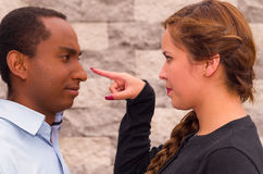 Headshot charming young interracial couple facing each other, she point her finger at his nose, brick wall background Stock Photography