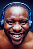 Headshot of cheerful music lover. Portrait of cheerful African American music lover in headphones wrinkling nose and smiling from ear to ear while looking at Royalty Free Stock Photography