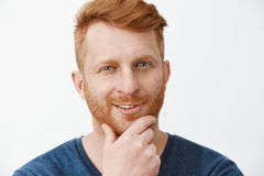 Headshot of creative and intrigued attractive redhead guy with bristle, rubbing beard and smirking, having great plan or royalty free stock photos