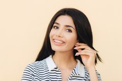 Headshot of cute lovely woman has broad smile, dark hair, keeps hand on ear, shows white teeth with braces, looks directly into ca. Mera, has happy expression stock image