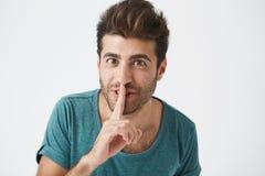 Headshot d'homme hispanique de sourire non rasé heureux dans des vêtements sport, tenant l'index aux lèvres, demandant à son amie Photo libre de droits