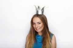 Headshot da mulher loura adorável nova com sorriso bonito na coroa feito à mão da princesa no fundo branco Fotos de Stock