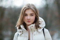 Headshot da mulher loura de vista natural nova bonita que levanta no parque da cidade da mola na roupa morna Emoções positivas li imagem de stock