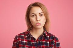 Headshot de femelle maltraitée avec les cheveux courts, lèvres de courbes avec mécontentement, étant offensé avec son ami sur qui Image stock