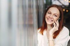 Headshot de l'employé féminin de sourire avec l'expression du visage gaie, instrument intelligent de téléphone d'utilisations pou images libres de droits