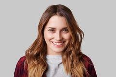 Headshot de la mujer sonriente hermosa con sonrisa amplia, estando en buen humor como presenta en la cámara, aislada sobre el fon Foto de archivo libre de regalías