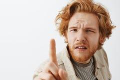 Headshot de ruivo engraçado confuso e questionado com cabelo desarrumado e de barba que são vesgo ao dobrar-se para e de picar fotos de stock royalty free