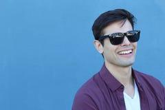 Headshot de um homem caucasiano em seus anos 20 meados de com os óculos de sol do desenhista tomados contra um fundo azul liso co Imagens de Stock Royalty Free