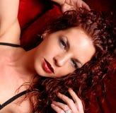 Headshot del encanto de la mujer en el sofá rojo Foto de archivo libre de regalías