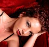 Headshot del encanto de la mujer en el sofá rojo Fotografía de archivo