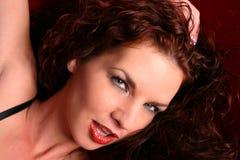 Headshot del encanto de la mujer en el sofá rojo Foto de archivo