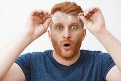 Headshot del individuo abrumado chocado e impresionado del pelirrojo con la barba, sacando los vidrios y sosteniendo el borde en  imagenes de archivo