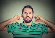 Headshot displeased young man plugging ears with fingers doesn't want to listen. Isolated on gray wall background Royalty Free Stock Image