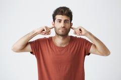 Headshot dokuczający elegancki włoski facet w czerwony t koszulowy patrzeć gderliwymi, końcowymi ucho z palcami pokazuje despekt  zdjęcia royalty free