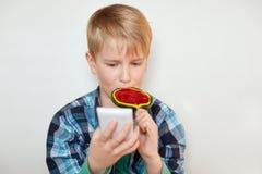 Headshot du beau petit garçon léchant la grande lucette dans un main et smartphone dans autre Une transmission de messages d'enfa Images stock