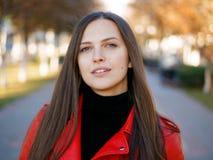 Headshot extérieur de femme élégante de brune de l'année 20s dans le manteau en cuir rouge sur le café ou le thé potable de pause images stock