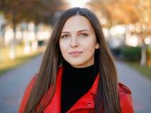 Headshot extérieur de femme élégante de brune de l'année 20s dans le manteau en cuir rouge sur le café ou le thé potable de pause photographie stock libre de droits