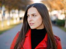 Headshot extérieur de femme élégante de brune de l'année 20s dans le manteau en cuir rouge sur le café ou le thé potable de pause photo libre de droits