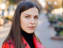 Headshot extérieur de femme élégante de brune de l'année 20s dans le manteau en cuir rouge sur le café ou le thé potable de pause image libre de droits