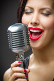 Headshot of female singer with closed eyes keeping microphone Stock Photos