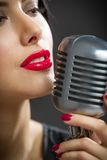 Headshot of female singer keeping microphone stock images