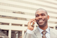 Headshot handsome happy laughing young business man talking on mobile phone Royalty Free Stock Image