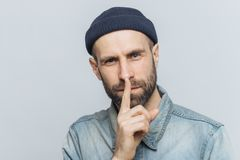 Headshot of handsome man with thick beard and mustache, has secret look, demonstrates silence sign, asks to be silent, isolated ov. Er grey background. Facial stock images