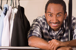 Headshot handsome young man standing inside wardrobe with clothes leaning across metal pole, smiling to camera, fashion Royalty Free Stock Photo