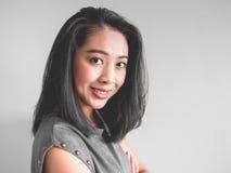 Headshot of happy woman. Headshot of happy Asian woman in grey dress stock image