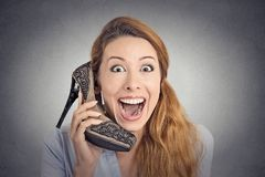 Headshot happy woman looking excited holding high heeled shoe as phone Royalty Free Stock Images