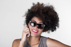 Headshot hispanic brunette rebel model with afro. Like hair wearing grey sleeveless shirt and sunglasses smiling to camera Stock Image