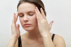 Headshot horizontal del modelo femenino joven con los ojos cerrados que se hacen masaje facial foto de archivo
