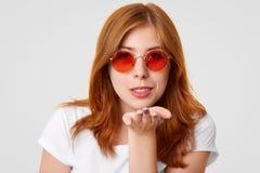 Headshot kokietka imbirowi żeńscy ciosy całuje przy kamerą, wyraża miłości chłopak, jest ubranym modnych round czerwonych okulary obraz stock