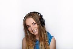 Headshot młoda urocza blondynki kobieta jest ubranym dużych czarnych fachowych monitorowanie hełmofony przeciw białemu studiu z ś Zdjęcia Royalty Free