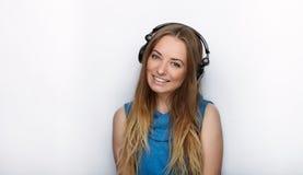 Headshot młoda urocza blondynki kobieta jest ubranym dużych czarnych fachowych monitorowanie hełmofony przeciw białemu studiu z ś Obrazy Stock