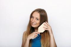 Headshot młoda urocza blondynki kobieta z ślicznym uśmiechem z gręplą w ręki muśnięciu jej włosy na białym tle Zdjęcie Royalty Free