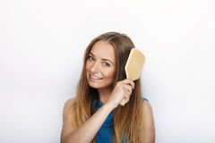 Headshot młoda urocza blondynki kobieta z ślicznym uśmiechem z gręplą w ręki muśnięciu jej włosy na białym tle Obrazy Royalty Free