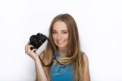 Headshot młoda urocza figlarnie blondynki kobieta z ślicznym uśmiechem w kobaltu koloru bluzce pozuje z czarną dslr kamerą na bie Zdjęcia Stock